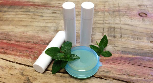 Homemade Lip Balm in Tubes with Peppermint Leaves.